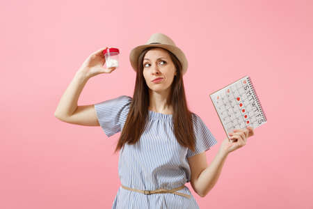 Portrait of sad woman in blue dress holding white bottle with pills, female periods calendar, checking menstruation days isolated on background. Medical healthcare, gynecological concept. Copy space