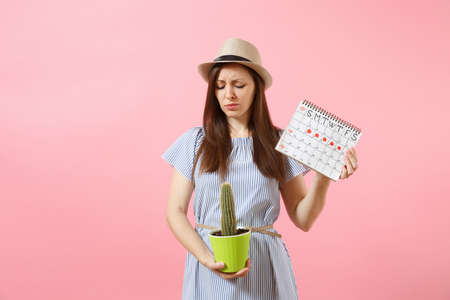 Sad sickness woman in blue dress holding green cactus, periods calendar for checking menstruation days isolated on pink background. Medical, healthcare, gynecological, tummy pain concept. Copy space