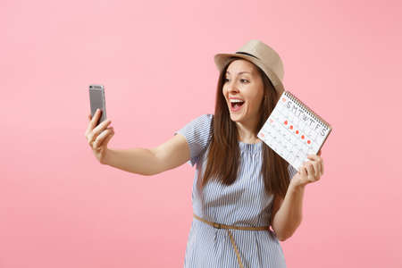 Excited woman in blue dress doing selfie on mobile phone, holding periods calendar for checking menstruation days isolated on pink background. Medical, healthcare, gynecological concept. Copy space