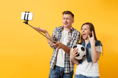 Young couple woman man, football fans doing selfie on mobile phone with monopod selfish stick, cheer up support team, soccer ball isolated on yellow background. Sport family leisure lifestyle concept Stock Photo