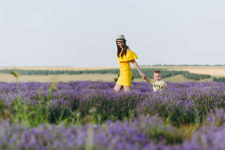 Young woman in yellow dress walk on purple lavender flower meadow field background, rest, have fun, play with little cute child baby boy. Mother, small kid son. Family day, parents, children concept