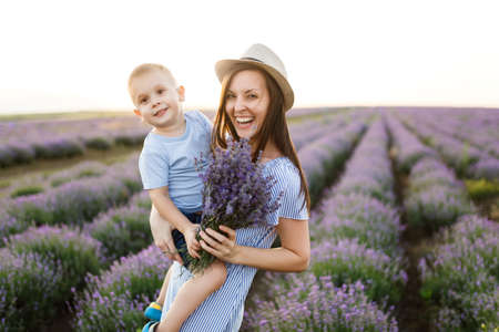 Young woman in blue dress hat walk on purple lavender flower meadow field background, rest, have fun, play with little cute child baby boy. Mother small kid son. Family day, parents, children concept Stok Fotoğraf