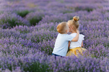 Playful little cute couple boy girl walk on purple lavender flower meadow field background, have fun, play, enjoy good sunny day. Excited small kids. Family day, children, childhood lifestyle concept