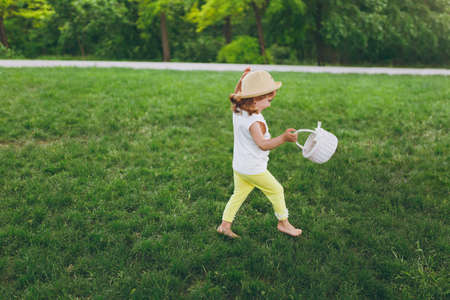 Pretty little cute child baby girl in hat with basket running, play and have fun on green grass lawn in park. Mother, little kid daughter. Mothers Day, love family, parenthood, childhood concept