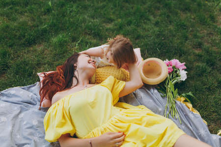 Joyful woman in yellow clothes play on green grass lawn in park, rest, have fun with little cute child baby girl. Mother, little kid daughter. Mothers Day, love family, parenthood, childhood concept