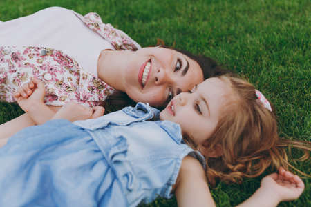 Smiling tender woman in light dress and little pretty child baby girl lie on green grass in park rest, have fun. Mother, little kid daughter. Mothers Day, love family, parenthood, childhood concept
