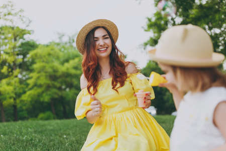 Laughing woman in yellow clothes play in park rest and have fun with little cute child baby girl hold soap bubble blower. Mother, little kid daughter. Mothers Day, love family, parenthood, childhood