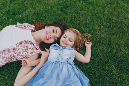 Smiling joyful woman in light dress and little cute child baby girl lie on green grass in park rest, have fun. Mother, little kid daughter. Mothers Day, love family, parenthood, childhood concept