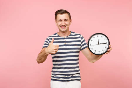 Portrait of smiling man in striped t-shirt showing thumbs up, holding round clock, copy space isolated on trending pastel pink background. Banque d'images - 105018777