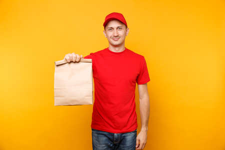 Man in red cap, t-shirt giving fast food order isolated on yellow background. Male employee courier hold empty paper packet with food.