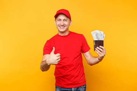Delivery man in red uniform isolated on yellow orange background. Professional male employee in cap, t-shirt courier or dealer holding bundle lots of dollars, cash money.
