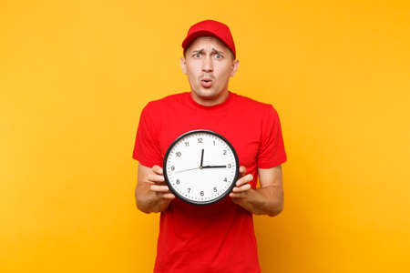 Delivery man in red uniform isolated on yellow orange background. Professional smiling male employee in cap, empty t-shirt working as courier or dealer holding round clock. Banque d'images - 105018517