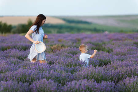 Young woman in blue dress walk on purple lavender flower meadow field background, catch up, have fun, play with little cute child baby boy. Mother, small kid son. Family day parents, children concept