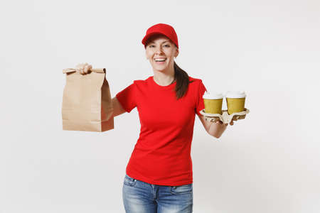 Woman in red cap, t-shirt giving fast food order isolated on white background. Female courier holding paper packet with food, coffee. Products delivery from shop or restaurant to home. Copy space Foto de archivo