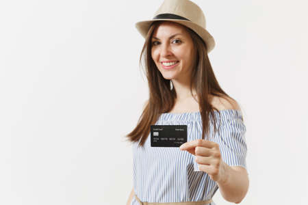 Young charming elegant woman in blue dress, hat with long brunette hair holding showing camera credit card isolated on white background. People lifestyle banking concept. Advertising area. Copy space Banco de Imagens