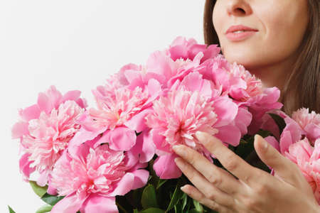 Close up cropped photo of tender woman holding, sniffing bouquet of pink peonies flowers isolated on white background. St. Valentines Day, International Womens Day holiday concept. Advertising area