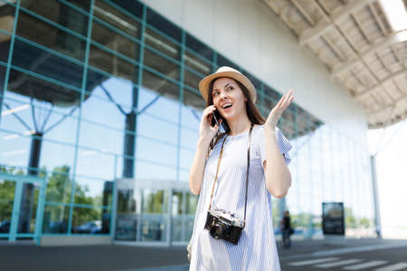Young traveler tourist woman with retro vintage photo camera spreading hands talk on mobile phone call friend booking taxi, hotel at airport. Passenger traveling abroad on weekend. Air flight concept