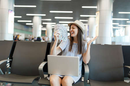 Young joyful traveler tourist woman working on laptop, hold bundle of dollars, cash money spread hands wait in lobby hall at airport. Passenger traveling abroad on weekend getaway. Air flight concept Stock fotó