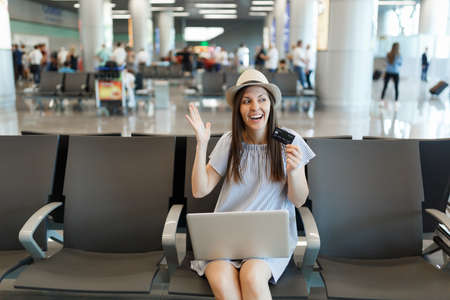 Young joyful traveler tourist woman working on laptop hold credit card spreading hands, wait in lobby hall at international airport. Passenger traveling abroad on weekends getaway. Air flight concept