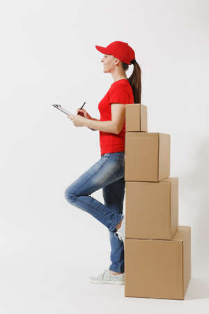 Full length of delivery woman in red cap, t-shirt isolated on white background. Female courier holding clipboard with papers document, blank empty sheet on empty cardboard boxes. Receiving package