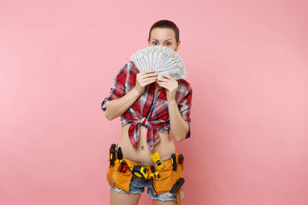 Young handyman woman in plaid shirt, denim shorts, kit tools belt full of variety instruments hold lots of cash dollar money isolated on pink background. Female doing male work. Renovation concept