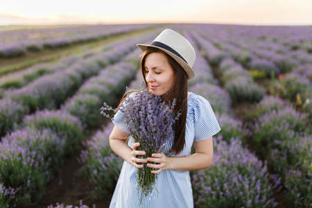 Young sensual beautiful woman in blue dress, hat on purple lavender flower blossom meadow field outdoors on summer nature background. Tender female near flowering bush with bouquet. Lifestyle concept