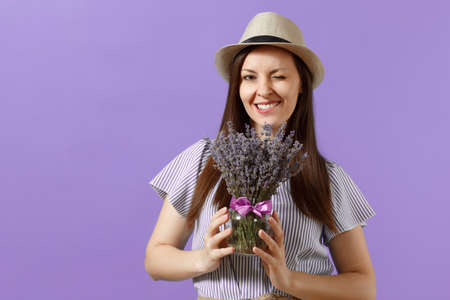 Portrait of happy young tender woman in blue dress straw hat holding bouquet of beautiful purple lavender flowers isolated on bright trending violet background. International Women Day concept
