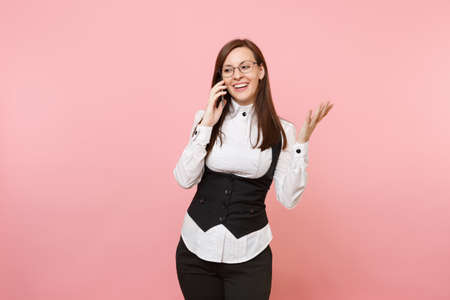 Young smiling business woman in glasses holding and talking on mobile phone spreading hands isolated on pastel pink background. Lady boss. Achievement career wealth. Copy space for advertisement