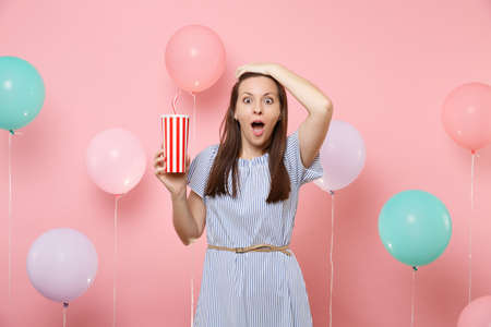 Portrait of shocked beautiful young woman wearing blue dress clinging to head holding plastic cup of cola or soda on pastel pink background with colorful air balloons. Birthday holiday party concept