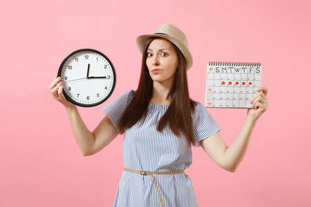 Shocked confused sad woman in blue dress holding round clock, periods calendar for checking menstruation days isolated on trending pink background.
