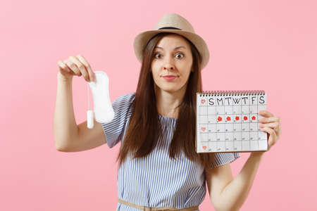 Woman in blue dress, hat holding sanitary napkin, tampon female periods calendar, checking menstruation days isolated on pink background.