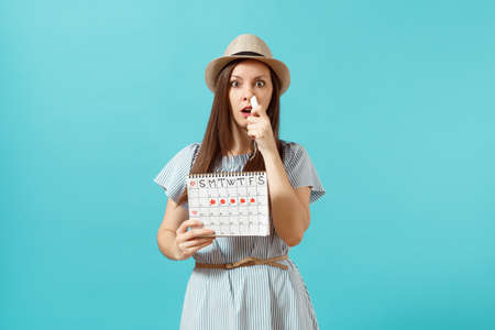 Sad shocked woman in blue dress, hat holding tampon in nose, female periods calendar for checking menstruation days isolated on blue background.