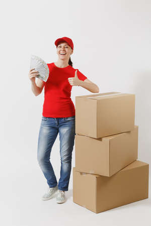 Full length of delivery woman in red cap, t-shirt isolated on white background. Female courier near empty cardboard boxes, bundle of dollars, cash money.