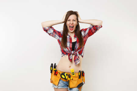 Strong young handyman woman in plaid top shirt, denim shorts, kit tools belt full of variety useful instruments isolated on white background. Stock Photo