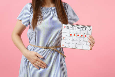 Portrait sad illness woman in blue dress holding periods calendar for checking menstruation days put hand on abdomen isolated on pink background.