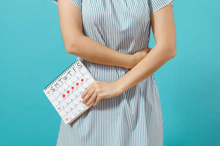 Cropped shot sickness woman in blue dress holding periods calendar for checking menstruation days put hand on tummy isolated on blue background.