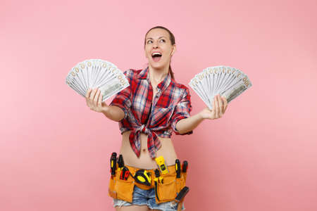 Young handyman woman in plaid shirt, denim shorts, kit tools belt full of variety instruments hold lots of cash dollar money isolated on pink background.