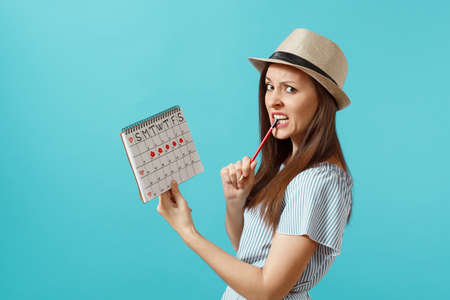 Portrait pensive woman in blue dress, hat holding red pencil, female periods calendar for checking menstruation days isolated on blue background. Stock Photo