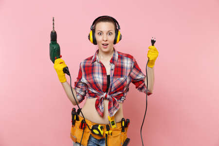 Energy sexy handyman woman in gloves, noise insulated headphones, kit tools belt full of instruments holding power electric drill isolated on pink background.