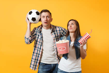 Young fun couple, woman man, football fans holding soccer ball, bucket of popcorn, plastic glass of cola, cheer up support team, isolated on yellow background. Stock Photo