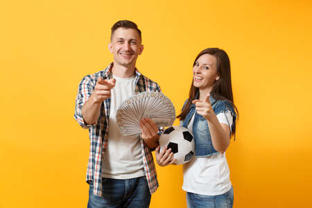Young win couple, woman man, football fans holding bundle of dollars, cash money, soccer ball, cheer up support team isolated on yellow background. Sport bet excitement ardor family lifestyle concept Stock Photo