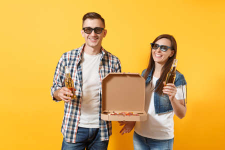 Young smiling couple woman man sport fans in 3d glasses cheer up support team holding beer bottles italian pizza in cardboard flatbox isolated on yellow background. Sport family leisure lifestyle