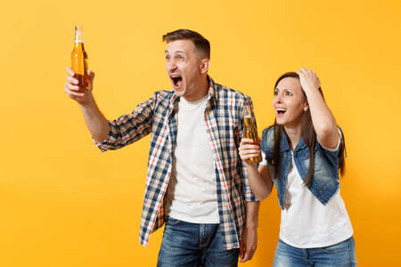 Young irritated couple woman man sport fan in casual clothes cheer up support team holding beer bottle clinging to head screaming isolated on yellow background.