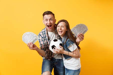 Junge gewinnen Paar, Frau Mann, Fußballfans halten Bündel von Dollars, Bargeld, Fußball, Aufmunterung Support-Team isoliert auf gelbem Hintergrund. Standard-Bild