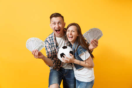 Young win couple, woman man, football fans holding bundle of dollars, cash money, soccer ball, cheer up support team isolated on yellow background. Stock Photo