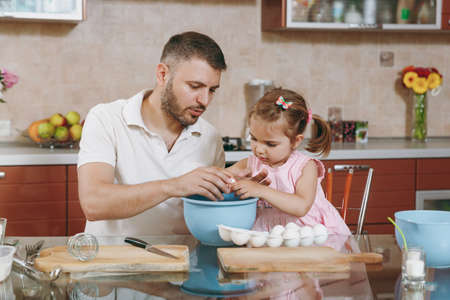 Little kid girl helps man to cook Christmas ginger cookies, breaks egg into bowl at table. Happy family dad, child daughter cooking food in weekend morning. Fathers day holiday. Parenthood childhood