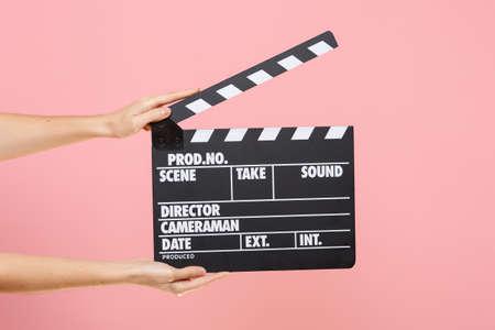 Chiuda sulla femmina che tiene in mano il regista classico chiaro vuoto nero film facendo ciak isolato su sfondo rosa pastello di tendenza. Concetto di produzione cinematografica. Copia spazio per la pubblicità Archivio Fotografico