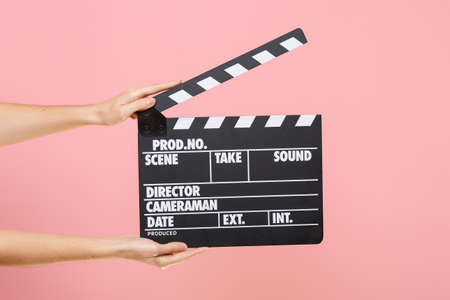 Close up female holding in hand classic director clear empty black film making clapperboard isolated on trending pastel pink background. Cinematography production concept. Copy space for advertising
