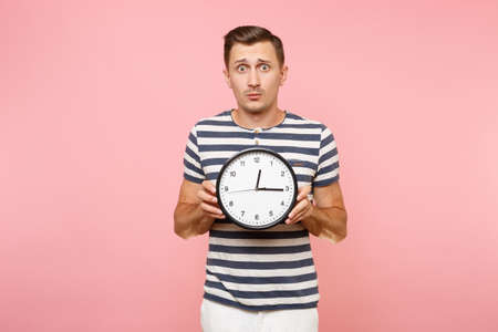 Portrait of shocked sad upset man wearing striped t-shirt holding round clock, copy space isolated on trending pastel pink background. People sincere emotions lifestyle concept. Time is running out Banque d'images - 105614341