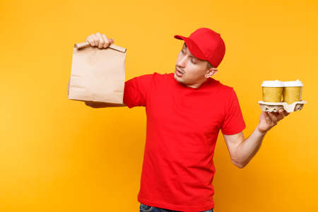 Man in red cap, t-shirt giving fast food order isolated on yellow background. Male employee courier hold paper packet with food, coffee. Products delivery from shop or restaurant to home. Copy space Banque d'images